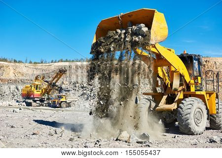 Heavy wheel loader extracting granite rock or iron ore at opencast mining quarry
