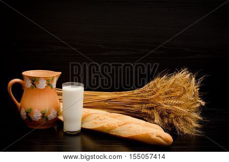 Batons a pitcher a glass of milk and a sheaf on a black background space for text