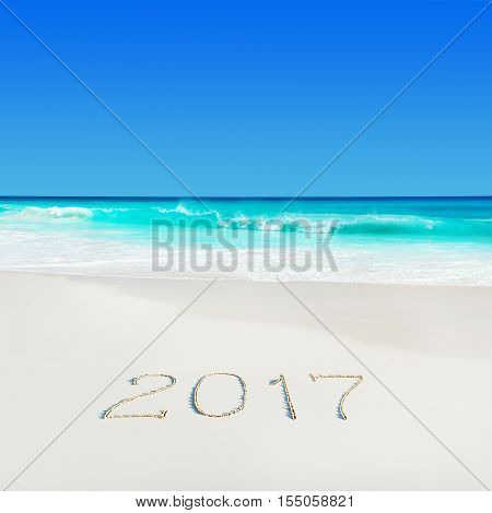 Turquoise ocean water at tropical white sandy beach and year 2017 happy new season caption on sand. Season vacation concept. Anse Georgette Praslin island Seychelles