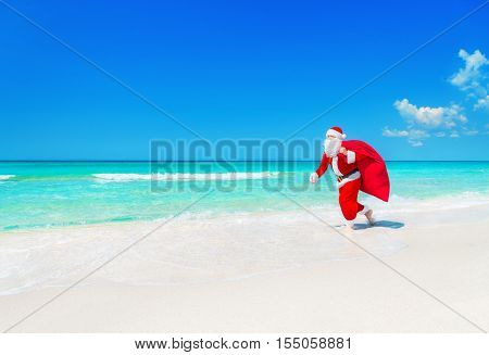 Christmas Santa Claus running with big gifts sack hurry on present it for children along tropical sandy ocean beach - New Year travel agencies price reductions concept
