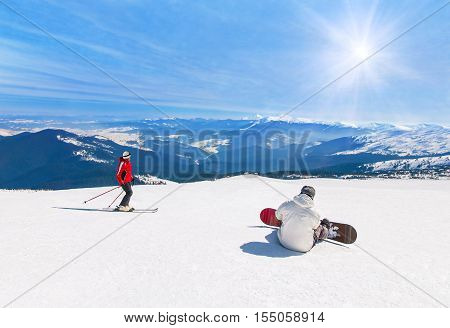 Skier and snowboarder skiing and snowboarding downhill in high snowy mountains against sun sunshine active winter sports holidays travel at ski health resort concept