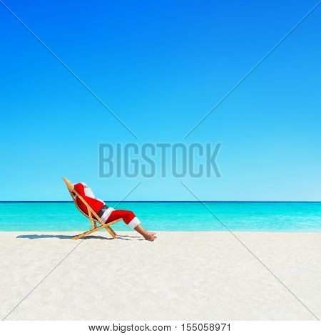 Santa Claus relaxing in sunlounger at ocean tropical sandy beach - Christmas and New Year travel vacation destinations concept