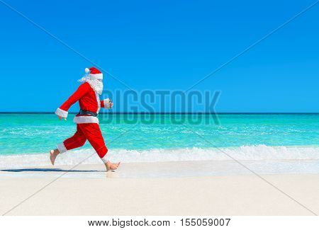 Santa Claus run at tropical sea beach sand against waves splashes Christmas and New Year's travel destinations concept