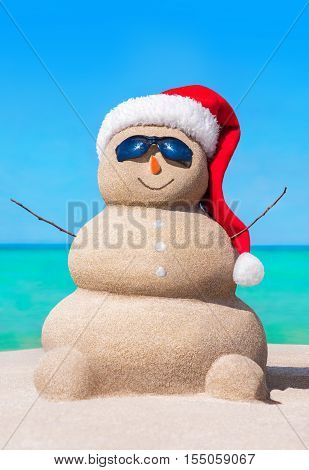 Positive funny winter snowman from sand in red Christmas hat and carrot at sunny hot sea beach - travelling in south countries for New Year's Day holidays concept