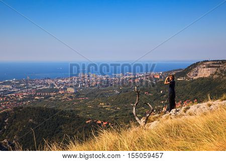 Hiker looking in binoculars enjoying spectacular view on Rosandra valley