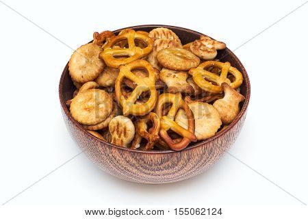 Mix of salty snacks (crackers and pretzels) in wooden bowl isolated on white background