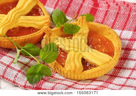 close up of apricot cakes with lattice on top on checkered dishtowel