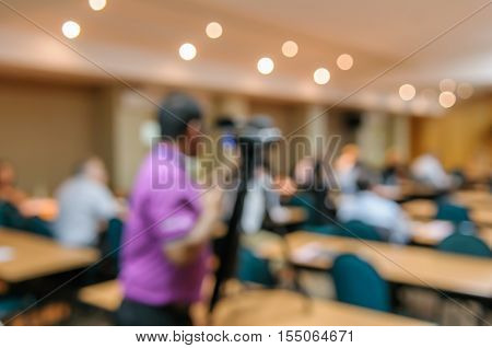 Abstract Blurred Image Of Cameraman Video Camera Recording In Conference Meeting