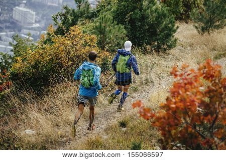 two men running mountain trail with backpacks for running. compression socks and taping on feet