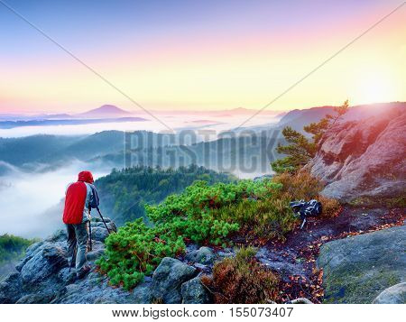 Photographer takes photos with mirror camera and tripod on peak of rock. Fall fogy landscape spring orange pink misty sunrise in beautiful valley below.