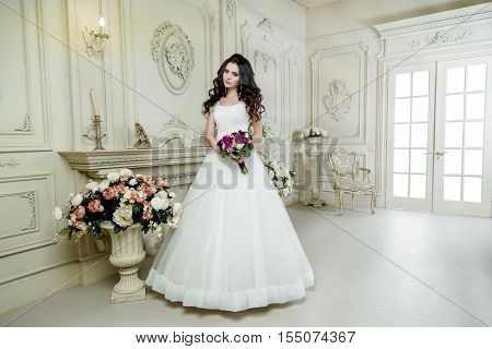 gorgeous bride in luxury wedding dress. Wedding make up and hairstyle, wedding  jewelry. gorgeous wedding bouquet of various flowers.