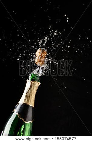 Cork flies out of champagne bottle isolated on black background