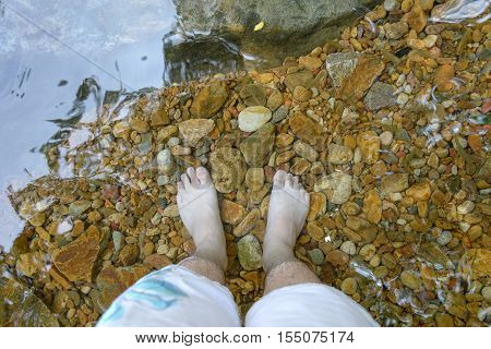 Man foot in nature water, relax time
