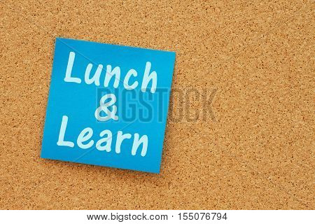 Lunch and learn notice Bulletin board with a blue sticky note with text Lunch & Learn