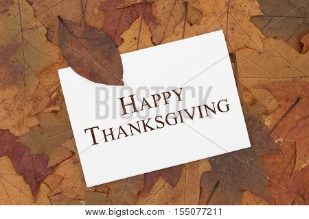 Happy Thanksgiving Greeting Card Some fall leaves and a greeting card with text Happy Thanksgiving
