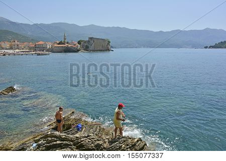 Budva, Montenegro - June 22nd 2016. Fishemen fish off the rocks in Budva. The old town stari grad can be seen in the background.
