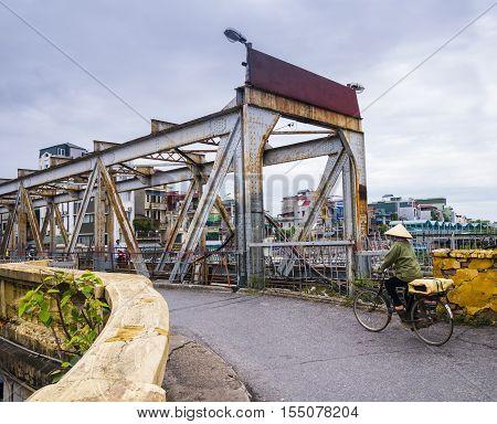 Crossing the Long Bien Bridge by bike, Hanoi, Vietnam