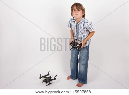 Boy holding a remote control is very disappointed because his drone unable to fly