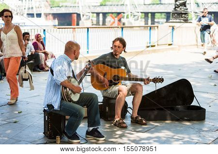 London UK - June 11 2006: Two young street musicians playing their banjo and classic guitar on the Thames river embankment to earn some money.