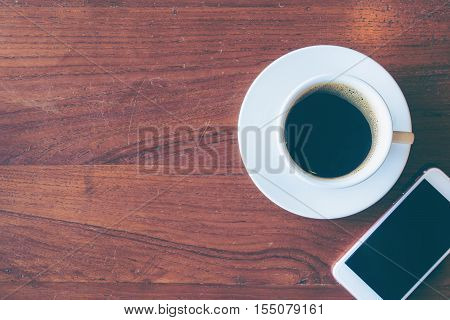 Top View Of A Cup Of Hot Coffee And Smartphone Put On Old Wooden Table Background