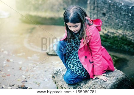 Pretty Little Girl Playing On A Rock At The Water's Edge
