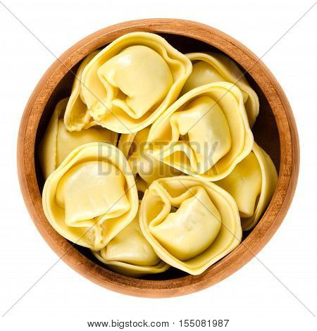 Tortelloni pasta in wooden bowl. Ring-shaped stuffed Italian dumplings with same shape as tortellini, but larger. Uncooked filled durum wheat semolina noodles. Macro food photo over white.