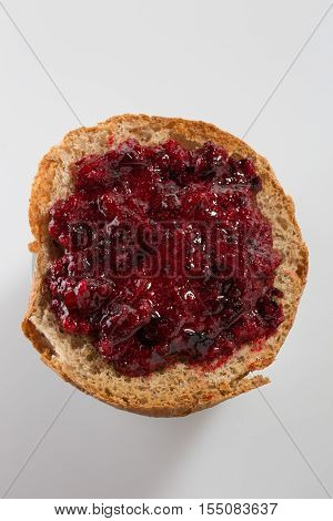 Roasted bread with layer of black currant jam on white background