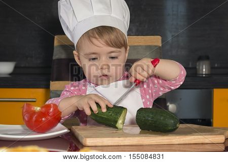 clouse-up portrait little cute girl playing in the kitchen with vegetables