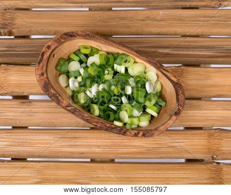 Organic green onion scallion in olive wood bowl on natural bamboo table