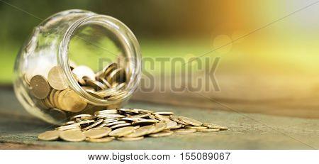 Golden coins in a glass jar - website banner of money savings concept