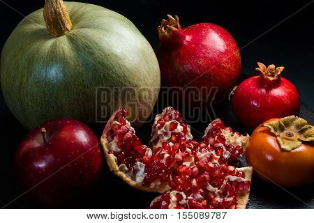 Various fruits of winter on black plate