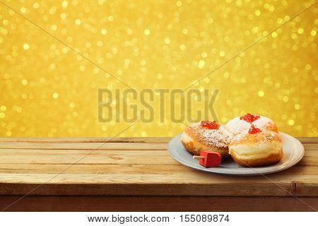 Hanukkah holiday sufganiyot on wooden table over bokeh background