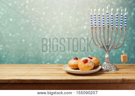 Hanukkah holiday sufganiyot and menorah on wooden table over bokeh background