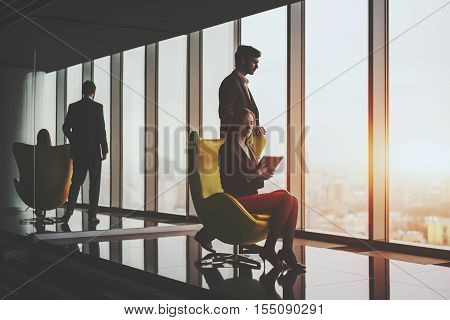 Young smiling successful man entrepreneur in formal business suite thoughtfully standing near yellow armchair with sitting female secretary with tablet on it