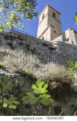 Alcala del Jucar, Spain - October 29, 2016: Passage along the river Jucar, right the church of San Andres, styles late Gothic and Neoclassic, take in Alcala del Jucar, Albacete province, Spain