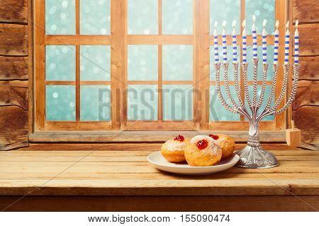 Hanukkah holiday sufganiyot with menorah on wooden table over window background