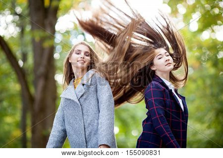 Two beautiful young girls in a coat in autumn park with long hair flying in the wind up