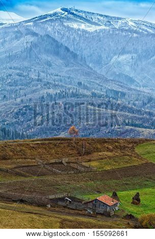 Volovets Ukraine - November 4 2016: House of the shepherd on the background of beautiful snow-capped peaks of Carpathian mountains autumn morning after a snowfall.