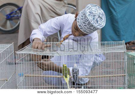 Omani Boy With A Bird Cage