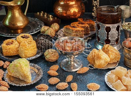 Large set of Eastern Arab Turkish sweets with cup of tea
