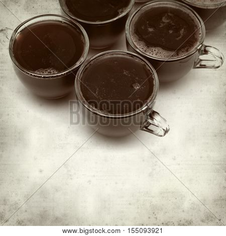 textured old paper background with idividual strawberry jelly portions in glass coffeecups
