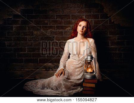 Portrait of a sexy sad redhead girl with kerosene lamp