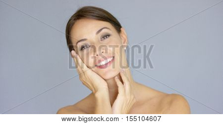 Happy young woman with hands on cheek