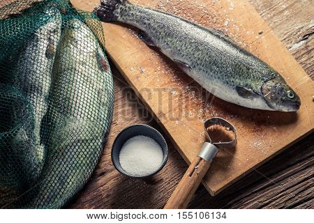 Preparing fish caught in freshwater on old wooden table