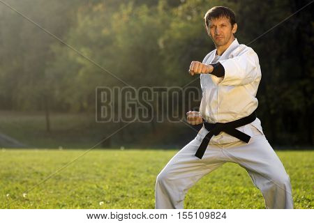 Karateist in white kimono with black belt is practicing karate shots outdoors in the park.