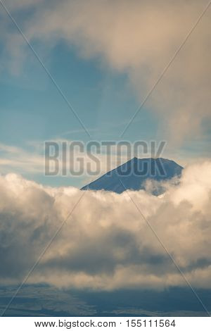 Hakone Japan - September 27 2016: Portrait of the summit of mount Fuji visible and encircled by bands of clouds as it is seen from Mount Komagatake. Valley in foreground.