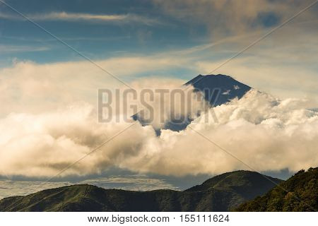 Hakone Japan - September 27 2016: Summit of mount Fuji visible and encircled by bands of rainy storm clouds as it is seen from Mount Komagatake. Valley and forest in foreground.