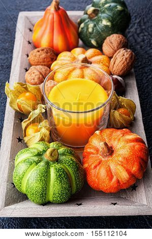Tray with autumn harvest and candle on textural background