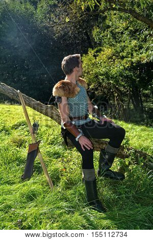 Young Medieval dressed man, sits on branch, hands on legs and looks to the back, arrow and curve stands besides