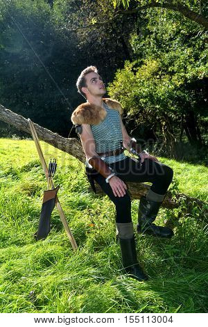Young Medieval dressed man, sits on branch, hands on legs and looks upwards, arrow and curve stands besides